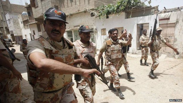 Paramilitary soldiers search in a neighbourhood after a gunfire attack on a security academy run by the Airports Security Force (ASF) in Karachi, 10 June 2014