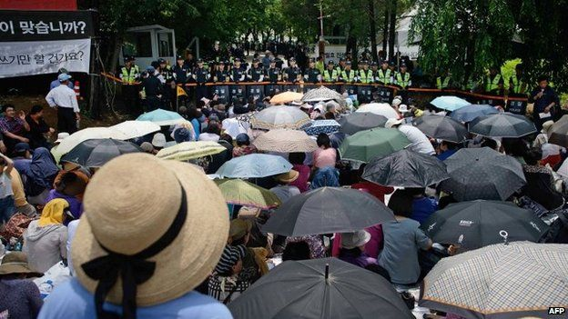 Followers sit before a line of police outside the compound of Yoo Byung-Eun, in Anseong on June 11