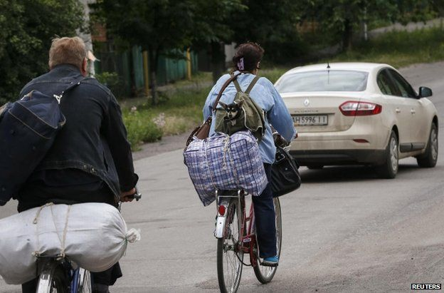 Local residents on bicycles flee from the fighting in eastern Ukraine, near the town of Sloviansk (12 June 2014)