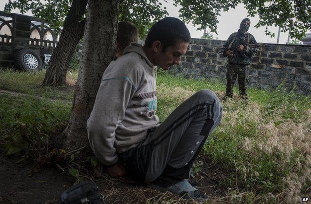 A rebel gunman guards suspected looters in Sloviansk, eastern Ukraine (12 June 2014)