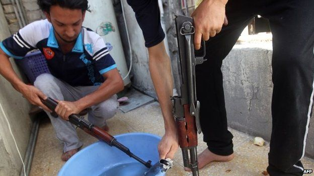 Iraqi Shia men clean weapons as they get ready to defend Sadr City district