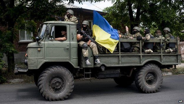 Ukrainian troops with a Ukrainian national flag sit atop a vehicle while they leave a scene of a battle in Mariupol, eastern Ukraine, Friday, June 13, 2014