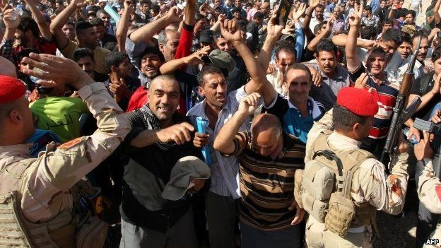 Iraqi men who volunteered to fight gather around buses in Baghdad, on June 16, 2014