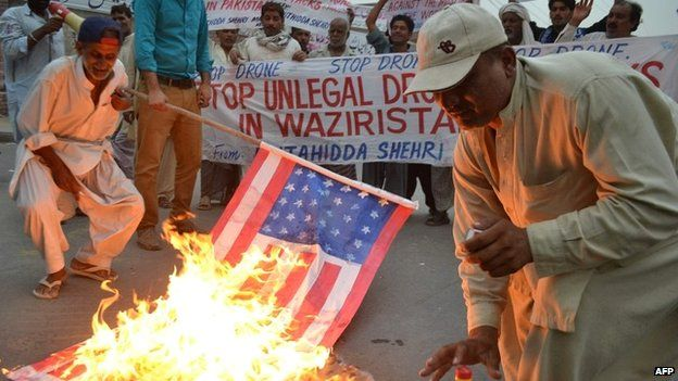 Pakistani demonstrators burn an American flag during a protest against a US drone strike - 12 June 2014