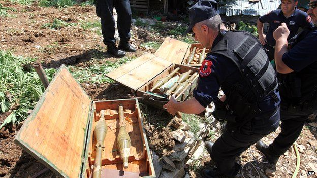 Albanian police officers display seized heavy guns in the lawless village of Lazarat on 20 June 2014