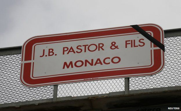 A black ribbon is seen on sign for the Pastor and Sons construction company in Monaco (22 May 2014)