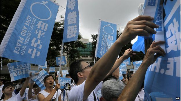 """Pro-democracy supporters raise banners that read: """"Occupy Central with Love and Peace,"""" during a kickoff ceremony of an referendum on democracy under a plan of Occupy-style protest in Hong Kong, on 20 June 2014."""