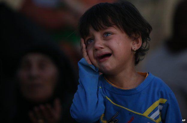 An Iraqi girl waits on a road near the Kurdish city of Irbil, 25 June