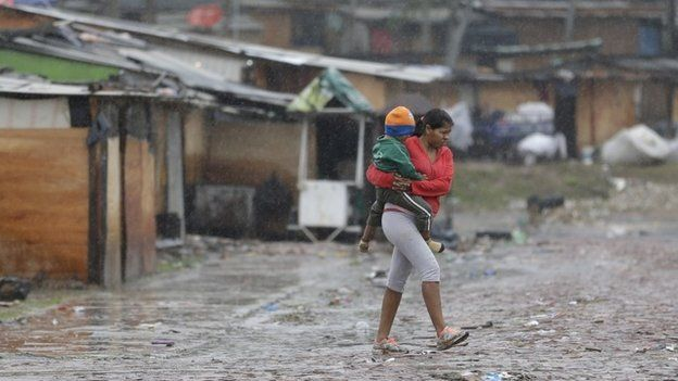 A woman carries her baby in a camp set up by people displaced by flooding