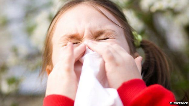A young girl sneezes