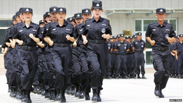 Policewomen from the Special Weapons and Tactics (SWAT) team run in formation during a graduation performance as members of an anti-terrorist patrol team in Xinjiang (June 2014)