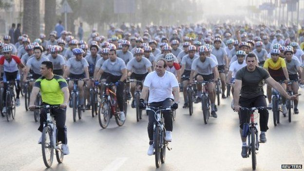 """Egypt""""s President Abdul Fattah al-Sisi (C, in white) with hundreds of bicycle riders in Cairo on 13 June"""