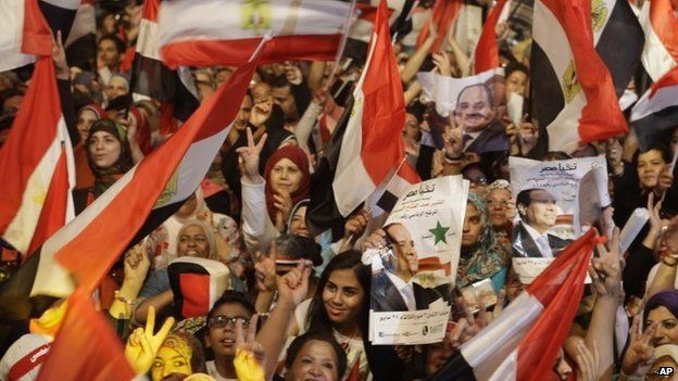 """Supporters of Egypt""""s president-elect Abdul Fattah al-Sisi wave national flags and his posters after his election win in Cairo on 5 June"""