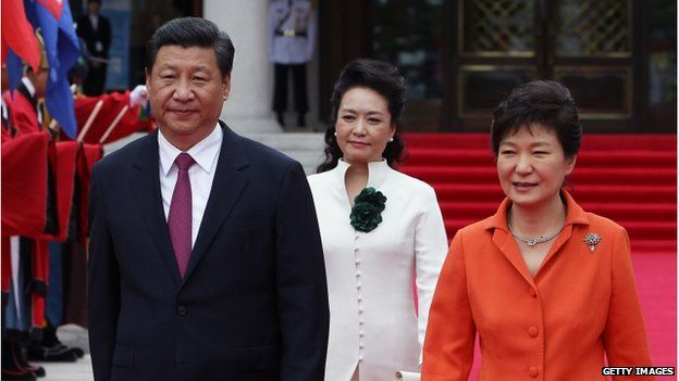 Chinese President Xi Jinping, his wife Peng Liyuan and South Korean President Park Geun-Hye walk towards a guard of honour during a welcoming ceremony held at the presidential Blue House on 3 July 2014 in Seoul, South Korea.