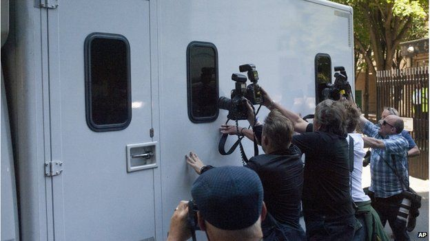 Press photographers trying to get pictures through the window of a prison van