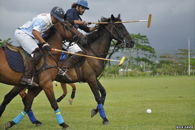 Two competitors challenge each other for the ball during a polo match in Jamaica - June 2014