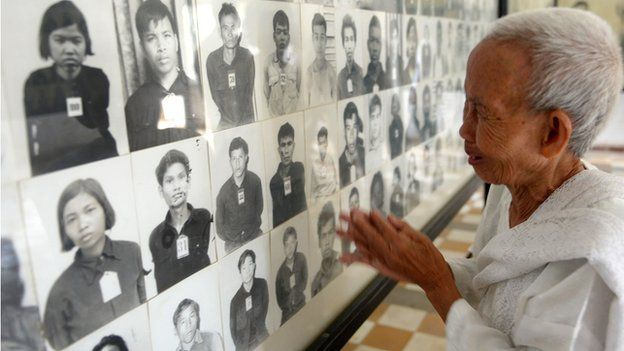 Woman looks at pictures of Cambodians killed during Khmer Rouge rule in the former Tuol Sleng Prison in Phnom Penh