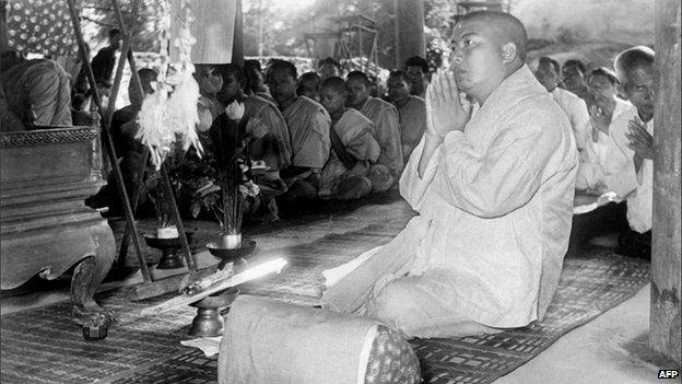 Former Cambodian King Norodom Sihanouk prays with monks after abdicating in 1955