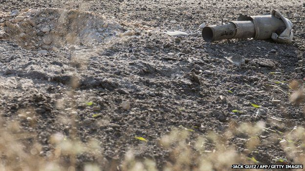 The remains of a rocket fired by Palestinian militants from the Gaza Strip lie on a road along the southern Israeli border with the Palestinian enclave on 10 July 2014.