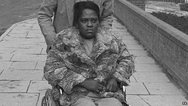 Cherry Groce being pushed in a wheelchair