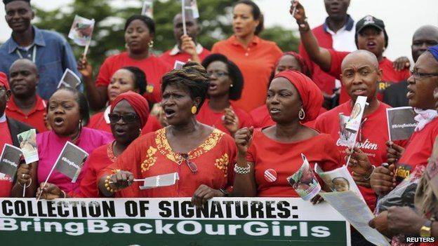 """File photo: People wearing red hold a banner at a speak-out session of a """"bring back our girls"""" rally in Lagos, Nigeria, 7 June 2014"""