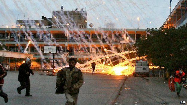 Palestinians run during an Israeli strike at a UN school in Beit Lahiya, northern Gaza, on 17 January 2009