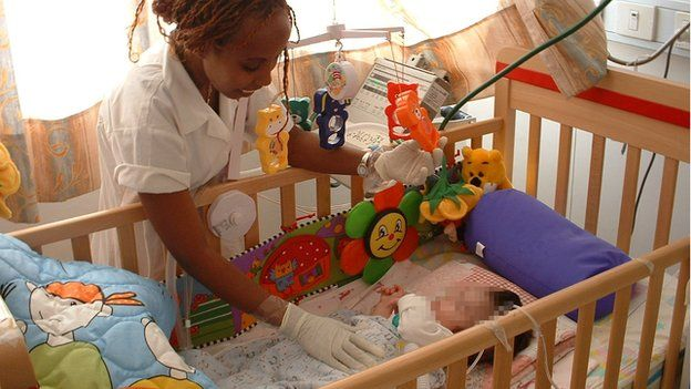 A nurse leans over the cot of a baby who is on a ventilator on a ward at Herzog
