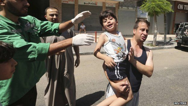 Man carries Palestinian boy wounded in Israeli air strike on house in Gaza City. 18 July 2014