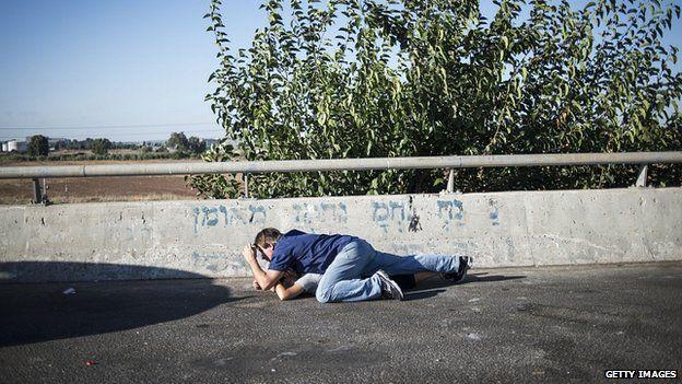 Israelis take cover on a motorway as siren sounds in Tel Aviv. 17 July 2014
