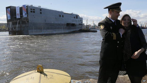 Stern of Mistral warship in St Petersburg and Russian naval officer with girlfriend