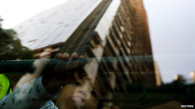 A child looks at a reflection of the Tower of David, 22 July 2014