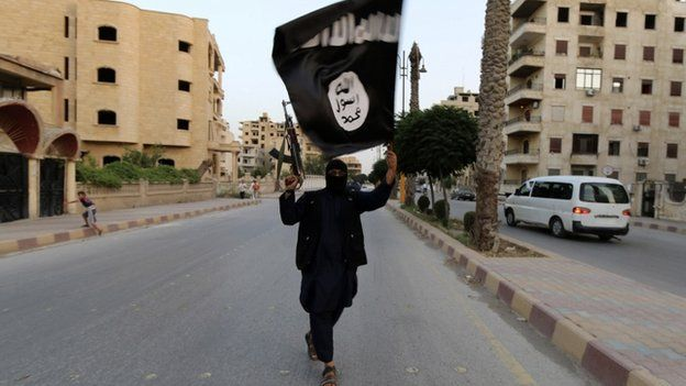 A member loyal to the Islamic State in Iraq and the Levant (ISIL) waves an ISIL flag in Raqqa on 29 June 2014.