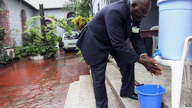 A Liberian man washes his hands as an extra precaution for the prevention of the spread of the Ebola virus before entering a church service in Monrovia, Liberia -27 July 2014