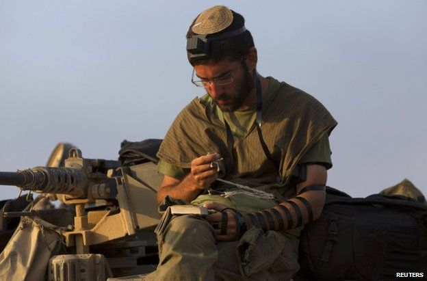 An Israeli soldier prays on top of a tank near the Gaza border, 29 July