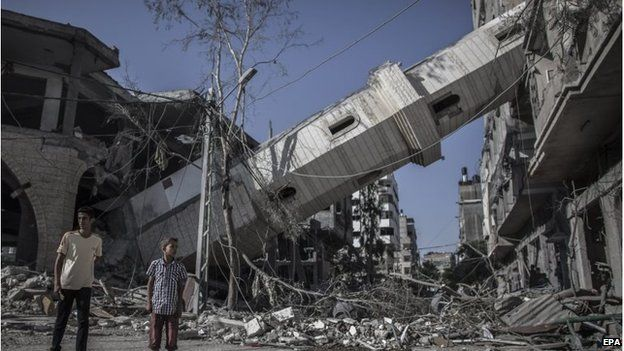 Palestinians walk next to the collapsed minaret of a mosque in Gaza City, 30 July 2014
