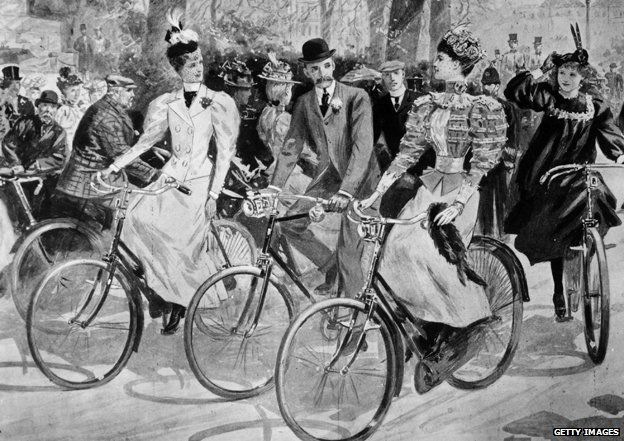 Two women and one man cycling in a park