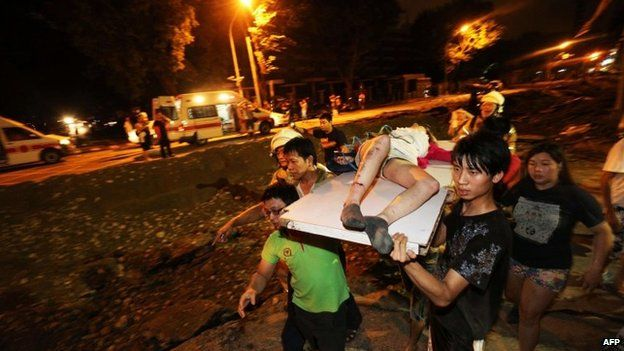Residents carry a wounded person following a blast in the city of Kaohsiung