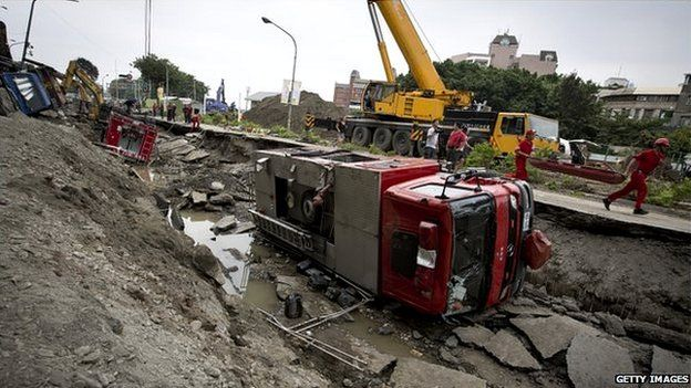 Damaged vehicles lie on the road after gas explosions in southern Kaohsiung on 1 August 2014 in Kaohsiung, Taiwan