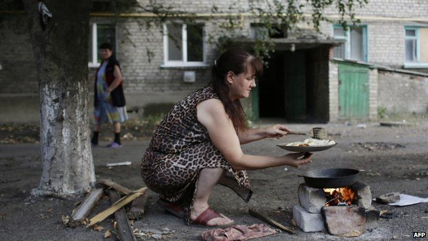 Woman cooks over campfire in Popasna, Luhansk region, retaken by government - 3 August