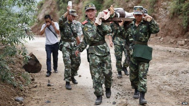 Local policemen help an injured resident in Zhaotong - 3 August 2014