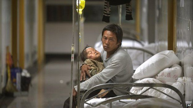 A man holds an injured child at a hospital in Yunnan province - 4 August 2014