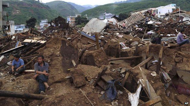Survivors rest on the ruins after a strong earthquake hit Ludian county, Zhaotong city, southwest China's Yunnan Province, on 4 August 2014