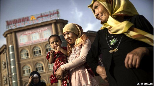 An Uighur woman walks with her baby at a market on 1 August 2014 in old Kashgar, Xinjiang Province, China.