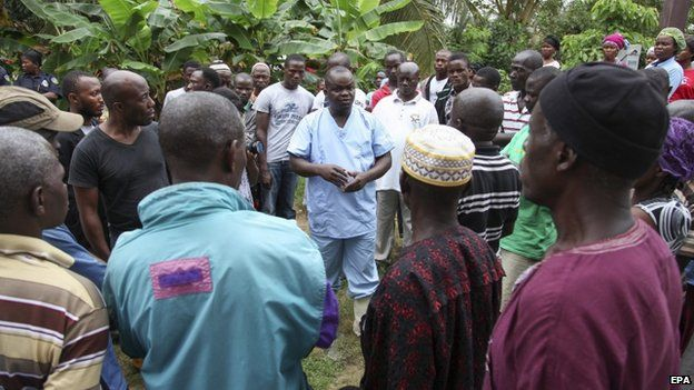 A Liberian nurse (C) addresses family members of dead Ebola victims before burial on the outskirts of Monrovia (6 August 2014)