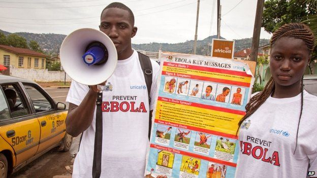 A couple taking part in a Ebola prevention campaign holds a placard with an Ebola prevention information message in the city of Freetown, Sierra Leone (6 August 2014)