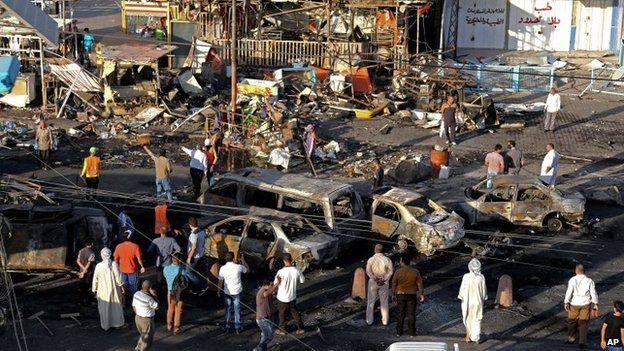 Iraqi civilians gather the morning after a string of car bombs tore through busy shopping streets in several neighbourhoods in Baghdad, Iraq, Thursday, Aug. 7, 2014.