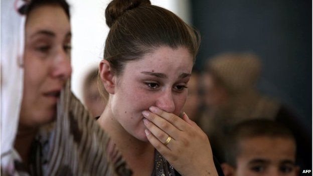 An Iraqi Yazidi woman who fled the violence in the northern Iraqi town of Sinjar, cries as she stands among others at a school where they are taking shelter in the Kurdish city of Dohuk, 05/08/14