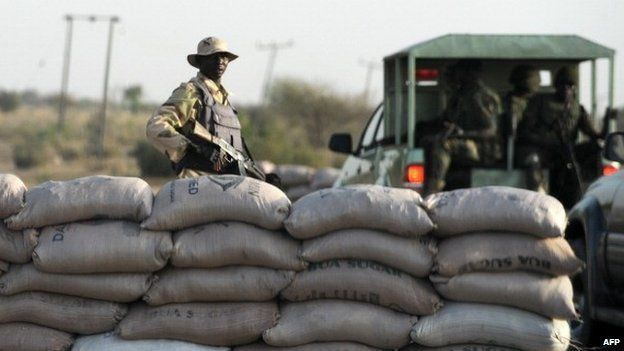 An officer of the Joint Military Task Force (JTF) stands beside sand bags at a road block in the north-eastern Nigerian city of Maiduguri on 30 April 2013