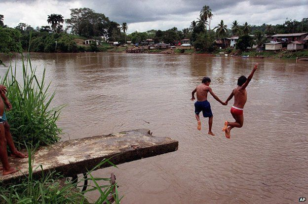 Two boys diving from a platform into the Darien Gap at Yaviza
