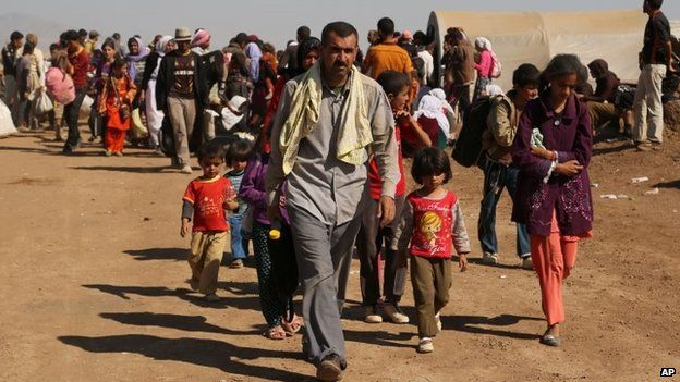 Displaced Iraqis from the Yazidi community cross the Syrian border